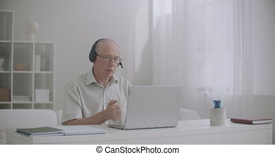 aged male boss is talking with employees by video call, giving orders, communicating online with office, distant working
