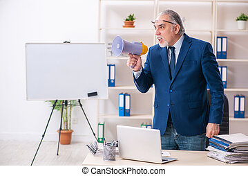 Aged male employee working in the office