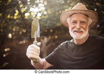 Aged male horticulturist is showing garden equipment - Waist...