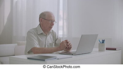 aged male lawyer is consulting client by internet, using laptop with web camera, sitting alone in his office or home, work remotely