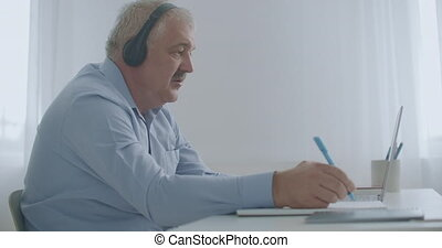 aged male lawyer is consulting client by internet, using online chat in laptop, writing notes and speaking, looking in webcamera