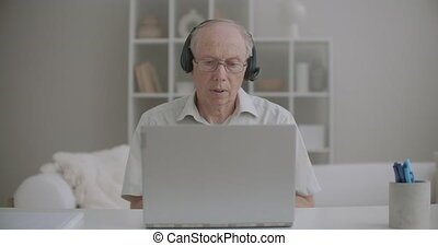 aged male professor is communicating by video call from home, using laptop and headphones, distant education and work remotely