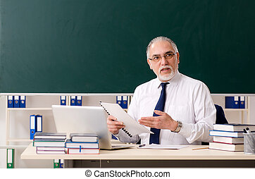 Aged male teacher in front of chalkboard