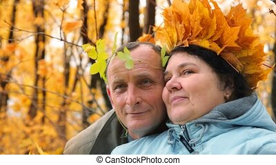 aged man and woman with leaves in park