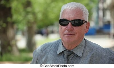 Aged man in black sunglasses sits on a bench and takes off them in a park