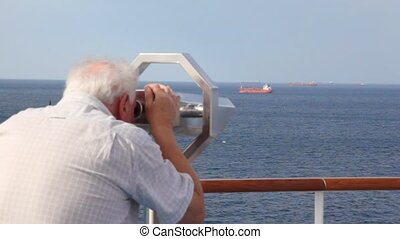 aged man looks through stationary binocular on deck of cruise ship