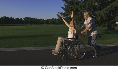 Aged man running while pushing wife in wheelchair