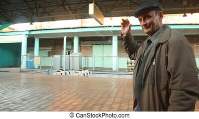 aged man seeing off comes near train and waives hand