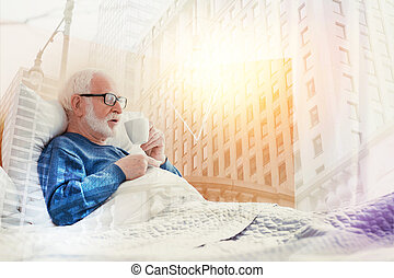 Aged man staying in bed and drinking hot coffee