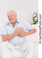 Aged man suffering with heart pain on a sofa