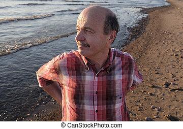 Aged man taking stroll alone on beach in summer season