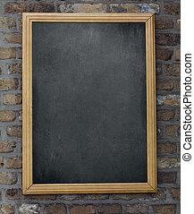 Aged menu blackboard hanging on brick wall