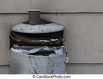 Aged outdoor metal broken grey trash waste bin - Old wall...