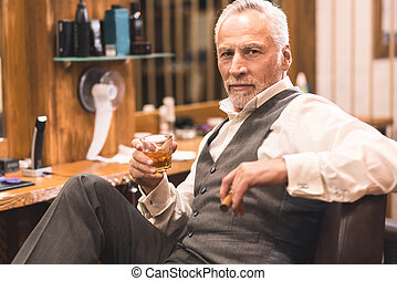 Aged owner enjoying free time in the barbershop