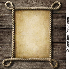 aged paper with rope frame on old wood background