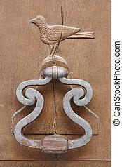 Aged spent metallic doorknob on a wooden door. Vertical