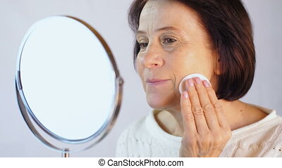 Aged woman cleans the face with a cotton pad - Cotton white...
