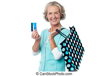 Aged woman displaying her cash card - Joyous shopaholic ...