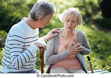 Aged woman having pain in the chest outdoors