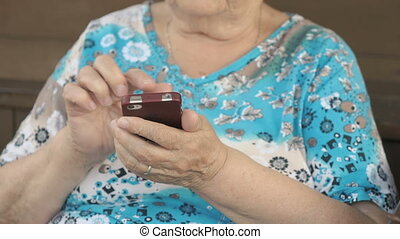 Aged woman holding a mobile phone