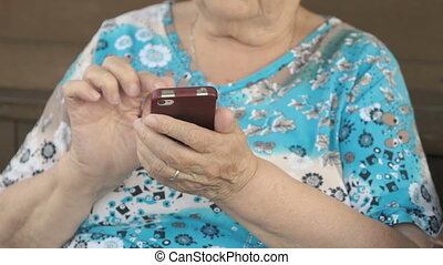 Aged woman holding a smartphone