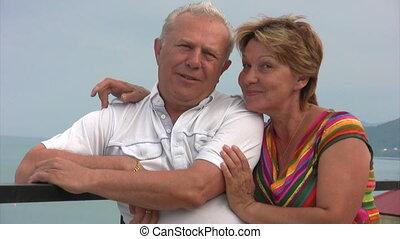 aged woman hugs her husband, stands near balustrade -...