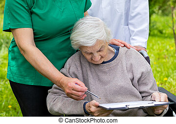 Aged woman in a wheelchair with medical assistance