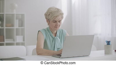 aged woman is working with laptop in home, feeling sharp ...