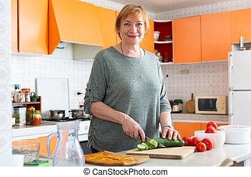 Aged woman preparing vegetable dish - Cheerful aged woman ...