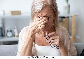 Aged woman taking off glasses rubbing eyelid suffers from eyestrain