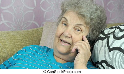 Aged woman talking with daughter on cellphone