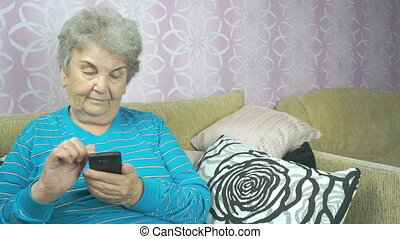 Aged woman using a mobile phone sits on a sofa