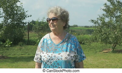 Aged woman walking in the park of garden