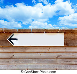aged wood arrow direction sign on blue sky