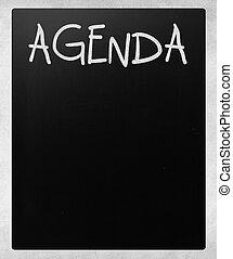 """AGENDA"" handwritten with white chalk on a blackboard"
