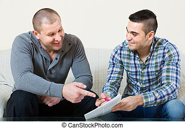 Agent and client with documents at home - Smiling male agent...