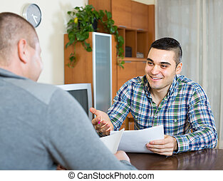 Agent and client with documents at home