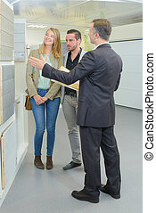agent and couple discussing tiles