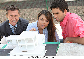 Agent and young couple with a model of a new development