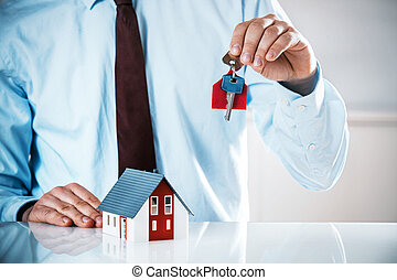 Agent Holding Key with Miniature Home on the Table