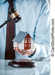 Agent Holding Miniature House with Wooden Gavel