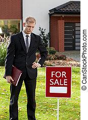 agent immobilier, debout, devant, maison
