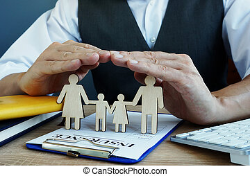 Agent protects family figures. Life Insurance policy on a desk.