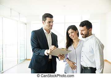 Agent Showing Contract To Couple In New House