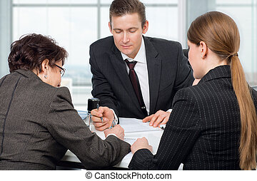 Agent signing documents with couple women