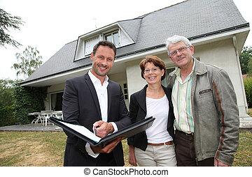 agente inmobiliario, con, pareja mayor, compra, casa nueva