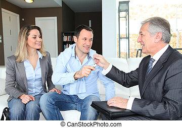 agente inmobiliario, dar, teclas de casa, a, joven, dueños