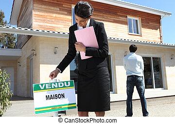 agente inmobiliario, poniendo, un, muestra vendida, delante de, un, propiedad