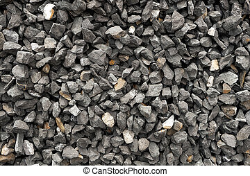 aggregate of dark gray and coarse stones crushed at a stone pit - gravel pattern