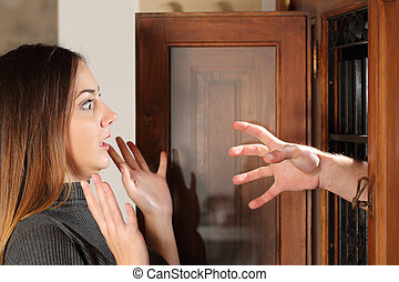 Aggression when a burglar try to attack a housewife with a hand through the door at home